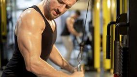 Den svettiga övrekroppen av att göra för grabb handtag-besegrar i idrottshallen som ser hans biceps, sporten arkivfoto