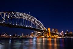 Den Sydney staden på natten med tänder upp av byggnader Arkivbild