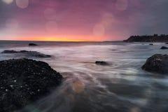 Den täckte muskeln vaggar och havet på solnedgången Fotografering för Bildbyråer