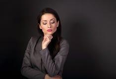 Den tänkande allvarliga affärskvinnan i grå färger passar att se ner på dar Arkivfoto