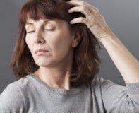 Den tänkande 50-talkvinnan angick om hennes hud- och hårkvalitet Arkivbild