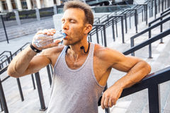 Den törstiga idrottsmannen tar en vila och ett dricksvatten, når han har kört Arkivfoton