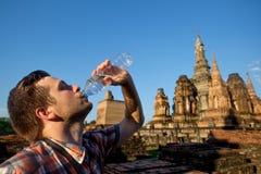 Den törstiga unga mannen dricker buteljerat vatten i buddhismtempel i Thailand royaltyfri foto