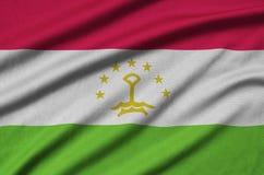 Den Tadzjikistan flaggan visas på ett sporttorkduketyg med många veck Baner för sportlag arkivfoton