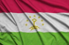 Den Tadzjikistan flaggan visas på ett sporttorkduketyg med många veck Baner för sportlag arkivbilder