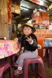 Den taiwanesiska infödda unga flickan säger nyfiket hälsningar till kameran royaltyfria bilder