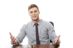 Den talande affärsmannen med huset modellerar vid ett skrivbord Arkivbild
