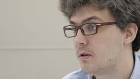 Den talande doktorn i exponeringsglas vänder mot upp ståenden på konsultation i klinikslut lager videofilmer
