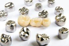 Den tand- keramisk, guld- och metalltanden krönar på vit bakgrund Arkivbild
