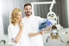 Den tand- specialisten undersöker en röntgenstråle av tanden Arkivbilder