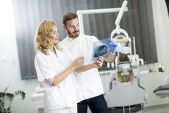 Den tand- specialisten undersöker en röntgenstråle av tanden Arkivfoto