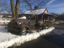 Den tappning rostade lastbilen gör den lantliga vedträställningen bredvid röd ladugård Royaltyfria Bilder