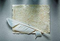Den tappning skrynkliga pappers- arkfjädern på grå färger ytbehandlar Royaltyfri Fotografi