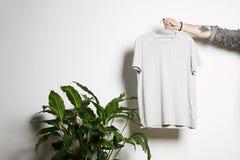 Den tatuerade manliga handen rymmer att hänga med den tomma vita t-skjortan från högvärdig tunn bomull på vit bakgrund Modellkopi royaltyfri fotografi