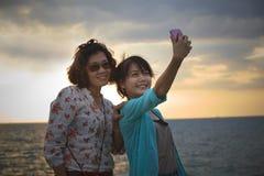 Den Teen och unga kvinnan tar ett foto vid mobil ringer på havssidan Royaltyfri Foto