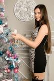 Den Teenag flickan dekorerar julgranen med julleksaker royaltyfri foto
