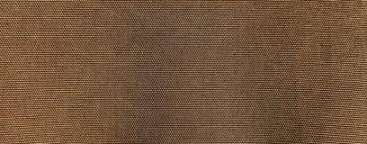 Den texturerade bakgrunden eller tapeten från grovt tyg av kakier färgar Royaltyfri Foto