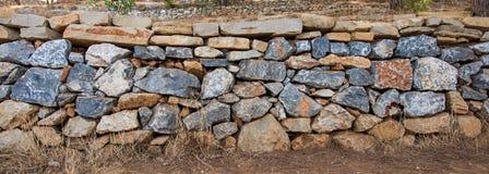 Den texturerade väggen fodrade med stora härliga mång--färgade stenar Arkivfoto