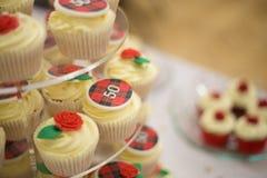 den 50th Bithday koppen bakar ihop med tarten och rosor Royaltyfri Fotografi