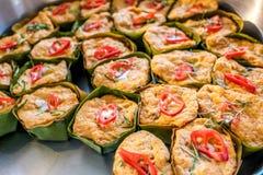 Den thailändska ångade curryfisken i bananbladkoppar dekorerade med den röda chili, (Hor Mok Pla) arkivbild