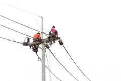 Den thailändska arbetaren på den elektriska polen för installerar isolerad ny kabel på w Fotografering för Bildbyråer