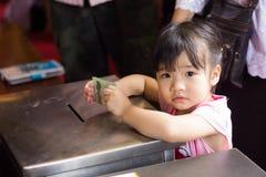 Den thailändska buddisten behandla som ett barn flickan donerar Arkivbilder