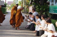 Den thailändska buddisten ger matofferings till den buddistiska munken Royaltyfri Bild