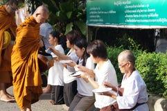 Den thailändska buddisten ger matofferings till den buddistiska munken Royaltyfria Bilder