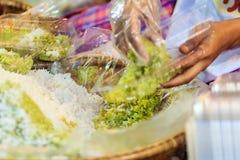 Den thailändska försäljaren säljer den strimlade riskornefterrätten till egenn Arkivbild
