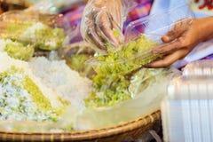 Den thailändska försäljaren säljer den strimlade riskornefterrätten till egenn Arkivfoton