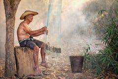 Den THAILÄNDSKA fiskaren som förbereder fiskekugghjulet är det, en livsföring av Tha Royaltyfri Foto