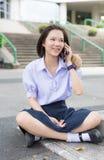 Den thailändska höga skolflickastudenten i skolalikformig sitter och pratar på mobil royaltyfri bild
