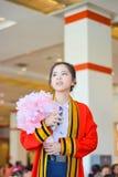Den thailändska högskolaflickan i akademisk kappa ser framåtriktat till framtiden i hennes avläggande av examendag Royaltyfri Foto
