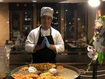 Den thailändska kocken i en dräkt vek hans händer Namaste, honom förbereder en nationell maträtt av skaldjur, risnudlar och spira royaltyfri foto
