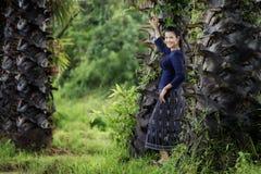 Den thailändska kvinnan i den traditionella dräktståenden för bygd under sockerpalmträden ror, Thailand Royaltyfria Bilder