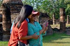 Den thailändska kvinnan och gamla kvinnor spelar mobilen i forntida byggnad Arkivfoto