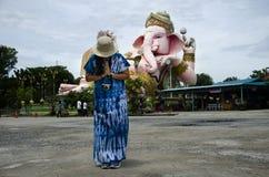 Den thailändska kvinnan som poserar för, tar fotoet och att be hälsa den Ganesh statyn Royaltyfria Foton
