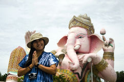 Den thailändska kvinnan som poserar för, tar fotoet och att be hälsa den Ganesh statyn Fotografering för Bildbyråer