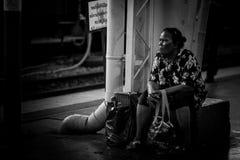 Den thailändska kvinnan väntar på avvikelsetid på den slutliga stationen för det head drevet i Bangkok Fotografering för Bildbyråer