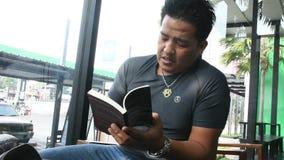 Den thailändska mannen sitter kopplar av läste boken, och tala med att dricka iskaffe i kafé shoppa stock video