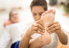 Den thailändska massageterapeuten masserar kvinnafoten Fotografering för Bildbyråer