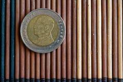 Den thailändska myntvalören är 10 baht lögn på träbambutabellen, godan för bakgrund eller vykortet - tillbaka sida Royaltyfria Bilder