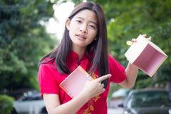 Den thailändska tonåriga härliga flickan i kinesisk klänning, det lyckliga nya året och öppnar askgåvan som är olycklig Royaltyfri Foto