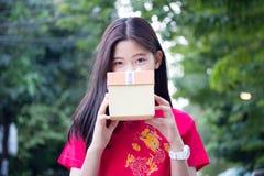 Den thailändska tonåriga härliga flickan i kinesisk klänning, det lyckliga nya året och ger gåvan, kopplar av och ler Arkivfoton