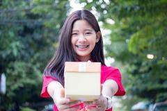 Den thailändska tonåriga härliga flickan i kinesisk klänning, det lyckliga nya året och ger gåvan, kopplar av och ler Royaltyfri Foto