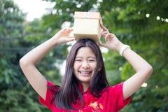 Den thailändska tonåriga härliga flickan i kinesisk klänning, det lyckliga nya året och ger gåvan, kopplar av och ler Arkivfoto