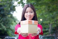 Den thailändska tonåriga härliga flickan i kinesisk klänning, det lyckliga nya året och ger gåvan, kopplar av och ler Royaltyfria Bilder