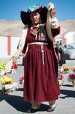 Den tibetana kvinnan som poserar i traditionell buddistisk klänning, och huvudbonaden cap hatten Arkivbild