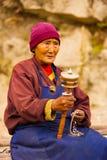 Den tibetana kvinnan vallfärdar be roterande Mani Wheel Arkivbilder