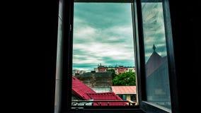 Den Tid schackningsperioden av rörande mörker fördunklar över staden till och med ett fönster arkivfilmer